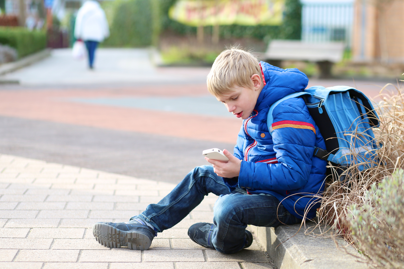 Teenager boy calling on mobile phone sitting outside of school
